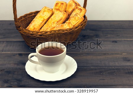 Basket with bread sticks, white porcelain cup and saucer standing on a wooden table background - small DoF focus put only to pier