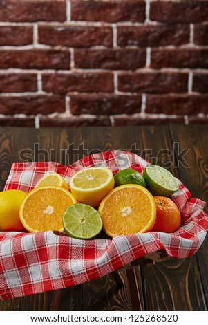 Basket with citrus fruit. Vitamin. Health. Freshness. Wood table. Brick background.