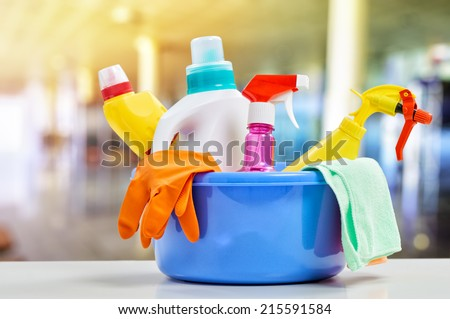Basket with cleaning items on blurry background - stock photo