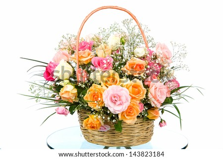 Basket with colored roses on white background - stock photo