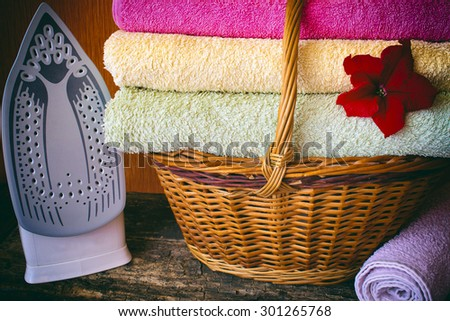 basket with colored towels red flower, iron, vignetting filter on the wooden background - stock photo