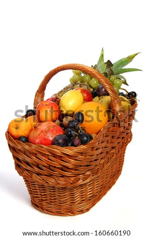 Basket with different fruits on the white background - stock photo