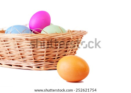 Basket with easter eggs and one on foreground