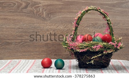 Basket with Easter eggs. Eggs for Easter - red, green and pink in a basket decorated with flowers. Background - the wooden board