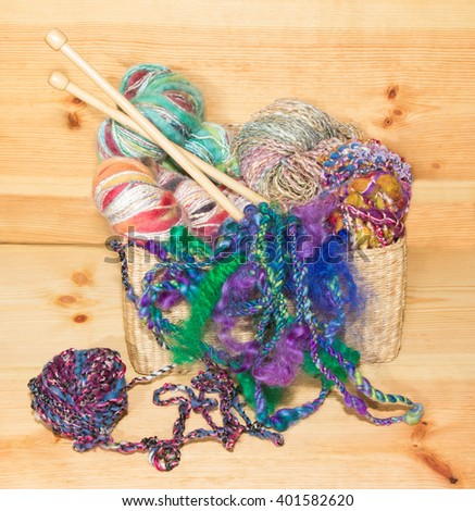 Basket with fancy art yarns and knitting needles on wood. - stock photo