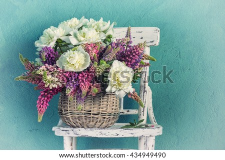 Basket with flowers peonies and lupins - stock photo