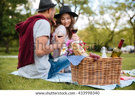 Basket with food and drinks standing near tender young couple drinking wine in park - stock photo
