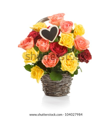 Basket with fresh colorful roses and heart on a stick on white - stock photo