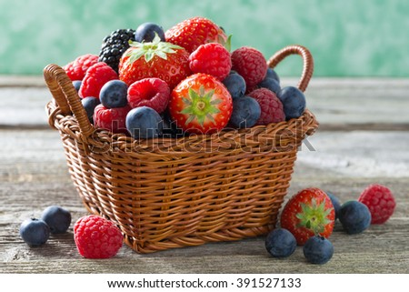 basket with fresh juicy berries on a wooden table, close-up, horizontal