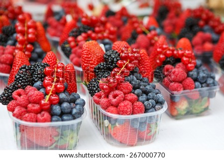 Basket with fresh juicy berries on farmer market. - stock photo