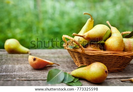 Basket with fresh pears with sliced pears on the table