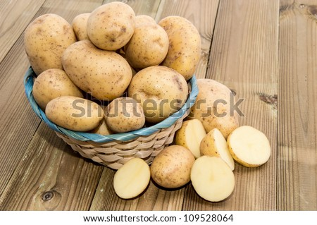 Basket with fresh Potatoes on wooden background - stock photo