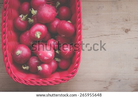 Basket with fresh radish on wooden background. Filtered image. - stock photo