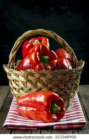 Basket with fresh red peppers on the table of the kitchen  - stock photo