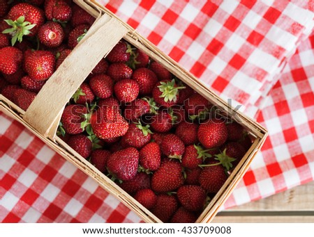 Basket with fresh tasty strawberries on a vintage tablecloth. Top view. - stock photo