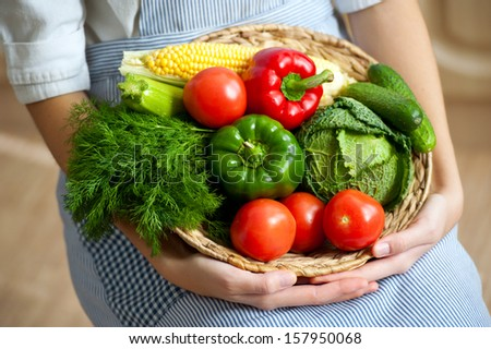 basket with fresh vegetables in the hands of women cooks