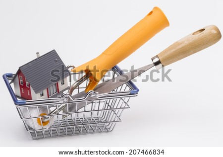 Basket with house and some tools, isolated on white background - stock photo
