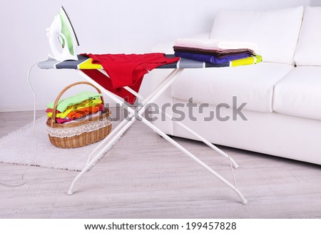 Basket with laundry and ironing board on light background