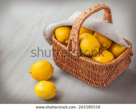 Basket with lemons on a gray wooden table - stock photo