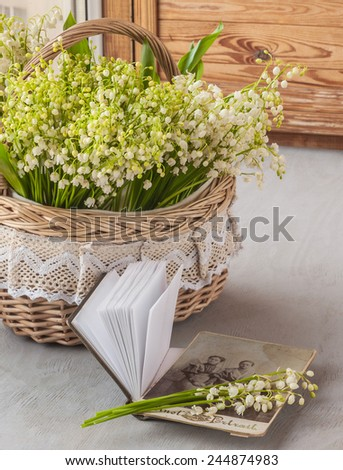 Basket with lilies of the valley (Convallaria majalis) next to notebook with old photographs on the window