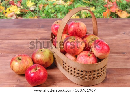 Basket with lying in her red apples on a wooden surface.