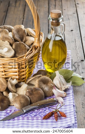 Basket with mushrooms, olive oil and ingredients for cooking on the table of the kitchen - stock photo