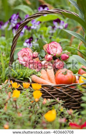 Basket with organic raw vegetables in wicker basket on the green grass and flowers. Outdoors. summer garden background. - stock photo