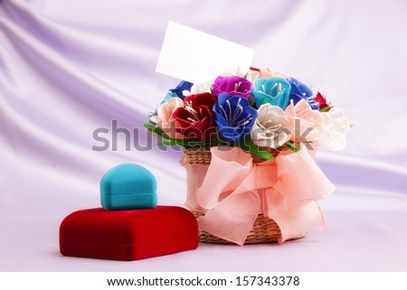 Basket with paper flowers, velvet boxes and blank card - stock photo