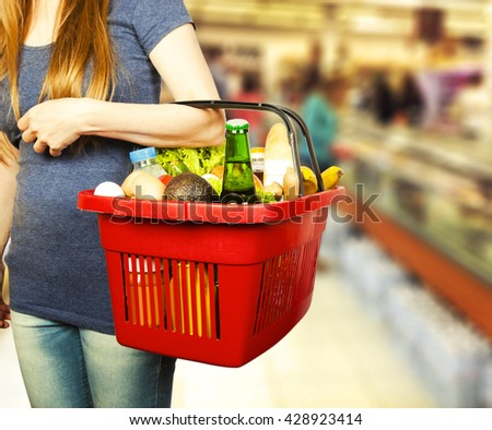Basket with products in woman hand - stock photo