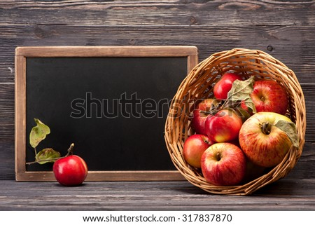 Basket with red apples and chalk board, horizontal