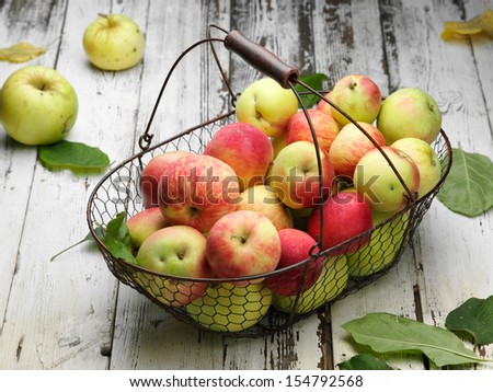basket with ripe tasty apples on wooden table - stock photo