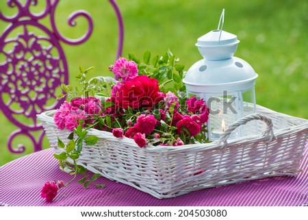 Basket with roses on a garden table - stock photo