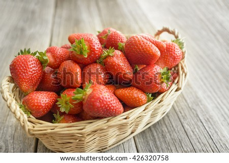 Basket with strawberries stands on a wooden table.