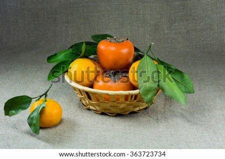 basket with tangerines and persimmons on sacking - stock photo