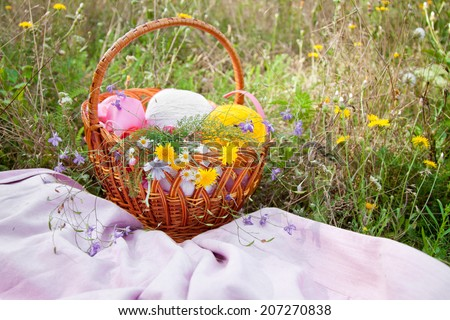 basket with thread tangles and flowers on the grass
