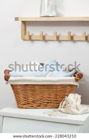Basket with towels and clothespins in the bag in laundry room - stock photo
