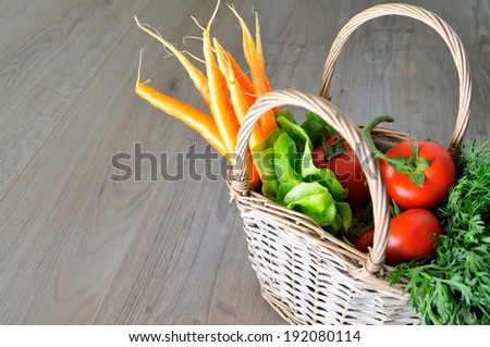 Basket with vegetables on the wooden kitchen table, copyspace avaliable  - stock photo