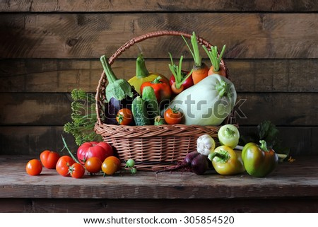Basket with vegetables: vegetable marrow, pumpkin, eggplant, pepper, carrots, beet, cucumbers and tomatoes. Vegetables in a basket. - stock photo