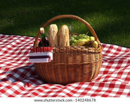Basket with wine, baguettes and fruits for picnic