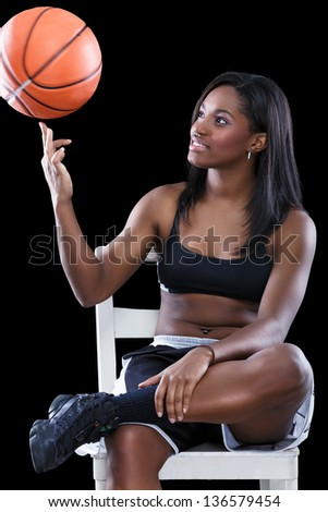 Basketball afro woman sitting and   have fun with ball - stock photo