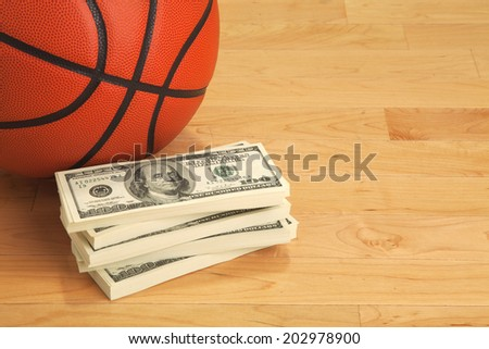 Basketball and stack of one hundred dollar bills on wooden court floor - stock photo