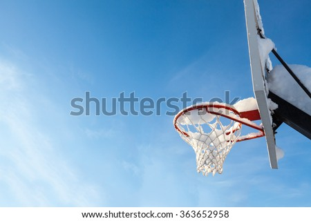 Basketball backboard from side with slam rim net after snowstorm - stock photo