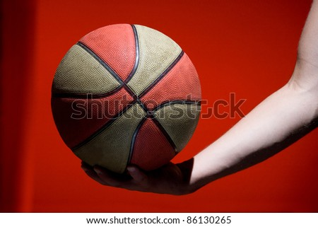 Basketball ball in hand isolated on red background - stock photo