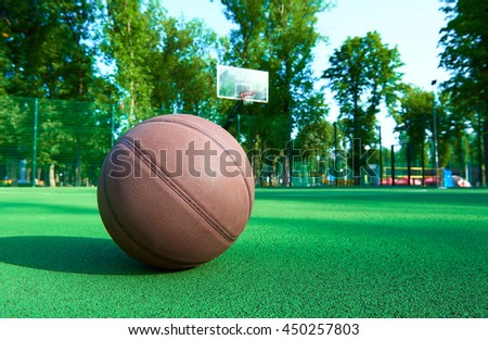Basketball ball on green field floor