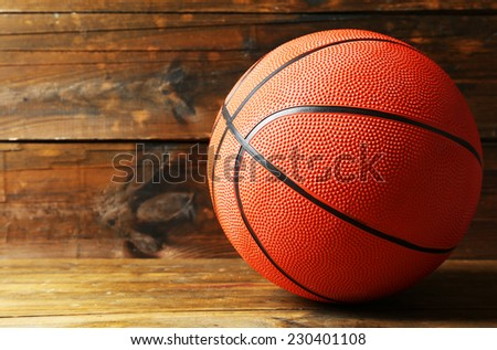 Basketball ball on wooden background - stock photo