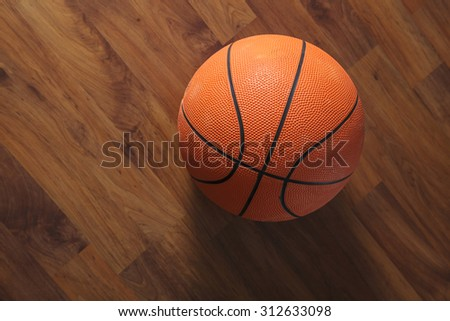 Basketball ball over wooden floor