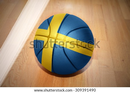 basketball ball with the national flag of sweden lying on the floor near the white line