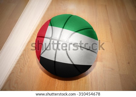 basketball ball with the national flag of united arab emirates lying on the floor near the white line - stock photo