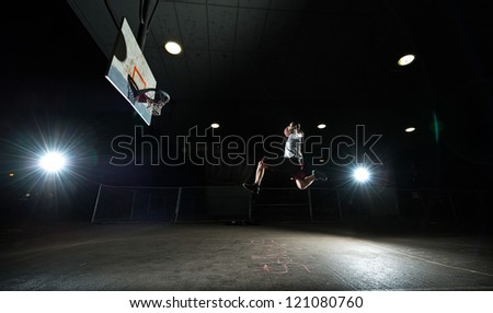 Basketball court at night with lights on, basketball player jumping and aiming at hoop - stock photo