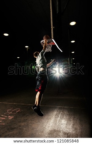 Basketball court at night with lights on, basketball player jumping and throwing a basket - stock photo